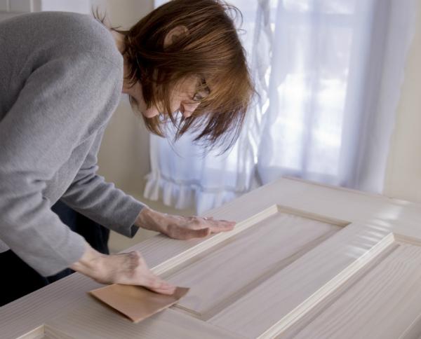 Holztuer mit Schleifpapier behandeln