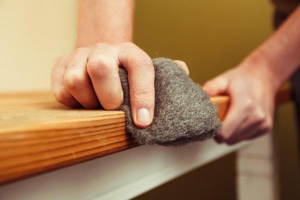 Ein Holztisch wird mit Stahlwolle abgeschliffen