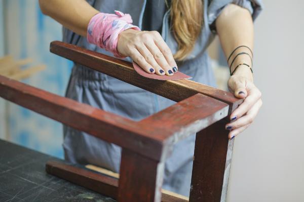 Eine Frau restauriert einen Stuhl
