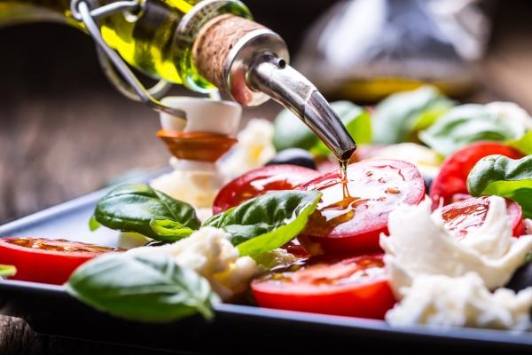 Mediterraner Salat aus Mozzarella, Kirschtomaten, Basilikum und Olivenoel