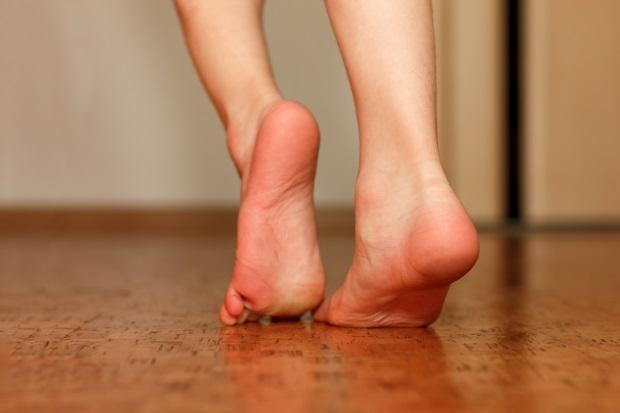 Zwei Füße laufen barfuß über einen Korboden. Korkboden Pflege und Reinigung.