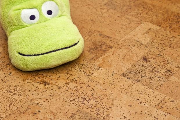 Ein flauschiger, grüner Hausschuh, der an ein Fabeltier erinnert, liegt auf dem Korkfußboden.