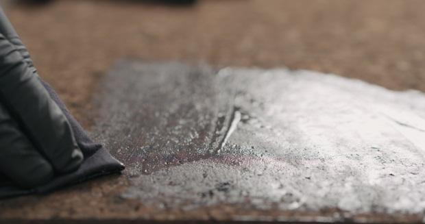 Eine Schutzlasur wird in den Korkboden eingearbeitet. Im Bild zu sehen ist eine Hand, die die Schutzversiegelung mit einem Tuch auf dem Boden verteilt. Korkboden Pflege und Reinigung.