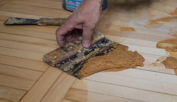 Handwerker bearbeitet Holzfläche mit Holzkitt