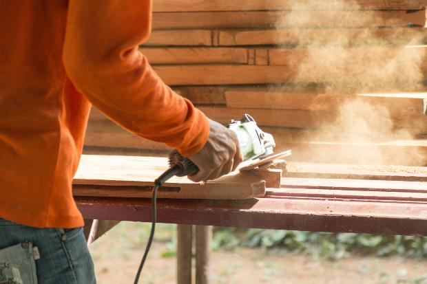 Mann schleift Holzwerkstück - es entsteht Holzstaub mit dem man Holzkitt herstellen kann