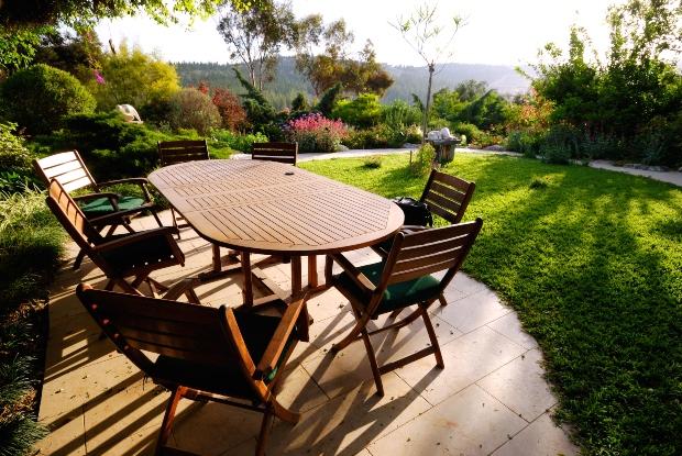 Gartentisch mit Stühlen in sommerlichem Garten