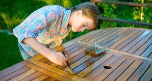 Junges Mädchen trägt Holzschutzmittel gegen Fäulnis auf
