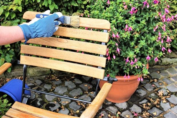 Stuhl wird mit Holzschutzmittel gegen Fäulnis lackiert