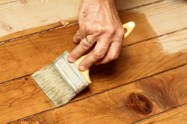 Mann ölt Holzboden mit Grundieröl für Holz