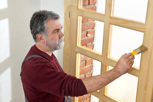 Mann streicht Holztür mit Grundieröl