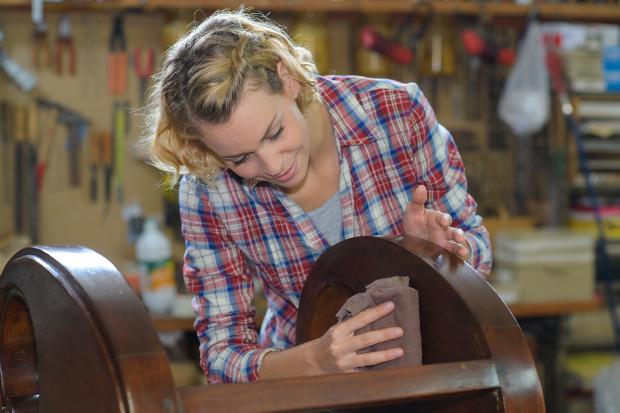 Frau poliert einen Holztisch mit einem Tuch - gewachstes Holz polieren ist nicht schwierig
