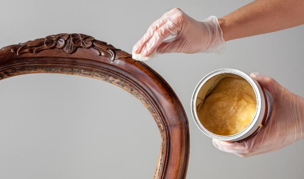 Person wachst Holzstuhl - gewachstes Holz polieren ist der folgende Schritt